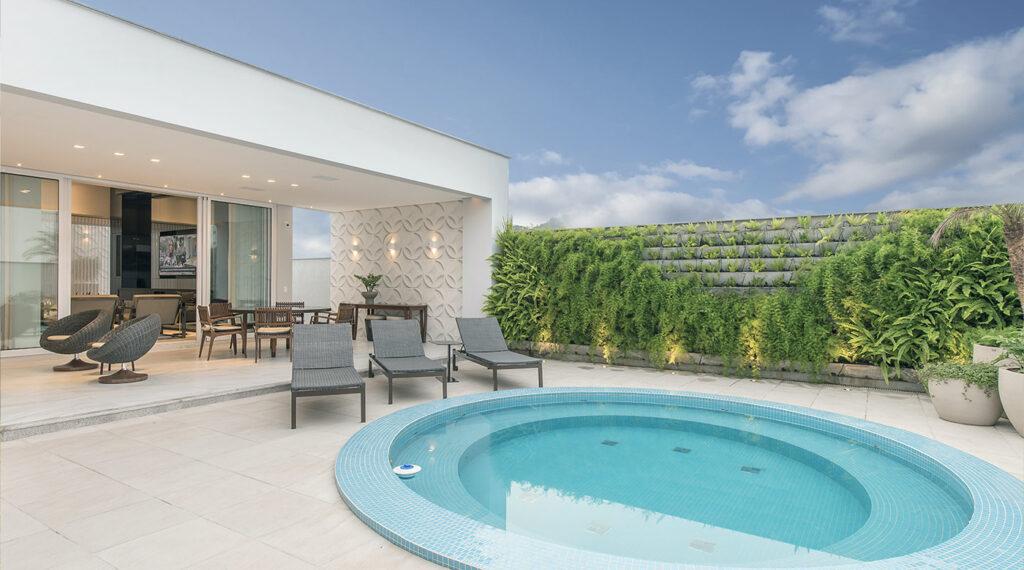 Parte externa da casa com piscina redonda e parede com jardim vertical