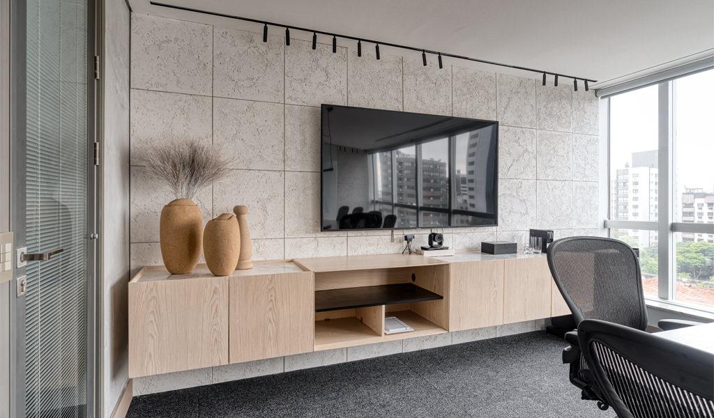 Sala de reuniões. Na parede em destaque, a televisão fica ao centro. Logo abaixo um armário que vai de um lado a outro da sala. A parede inteira é revestida com Ártemis, revestimento cimentício da Palazzo.
