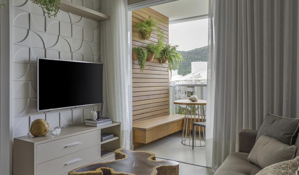 Pequena sala de TV integrada com varanda Gourmet. Atrás da televisão, o revestimento Nya, da Palazzo, reveste a parede inteira.
